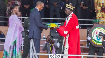 Rwanda's President Paul Kagame (C) receiving national symbols from the Chief Justice Prof. Sam Rugege (R)